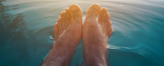 male-feet-in-outdoor-swimming-pool-PGGUFQH
