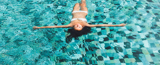 woman-relaxing-in-luxury-swimming-pool-in-white-bi-CVZERAU
