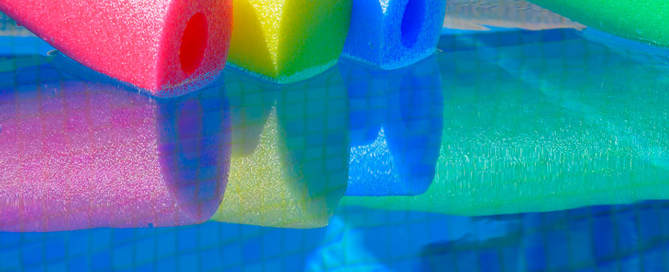 multicoloured-pool-noodles-and-turquoise-water-7RXNJLE